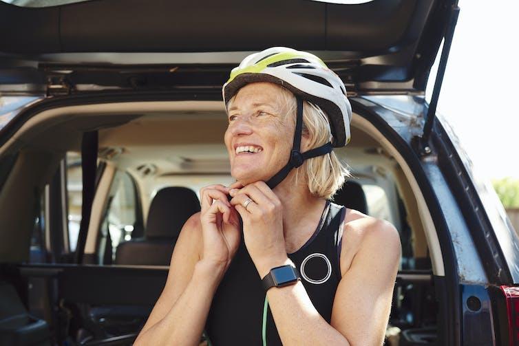 Une femme aux cheveux gris enfile un casque de vélo. Elle porte une montre Apple.