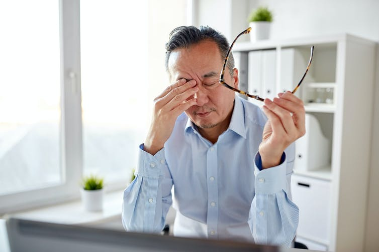 Man in a home office takes his glasses off and rubs his eyes.