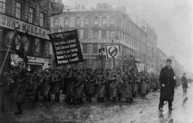 Russian men marching in the street with banners.