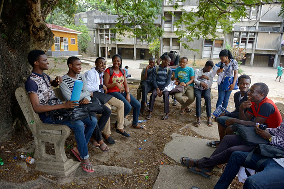 Young women and men (students) seated under a tree, discussing happily.