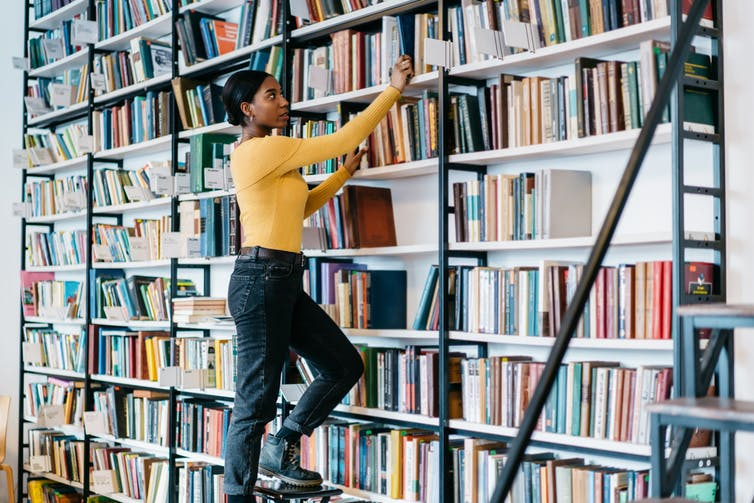 Woman taking books down from a shelf in the library.