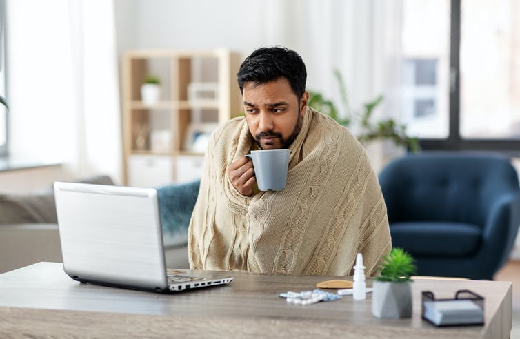 A man with a cold, wrapped in a blanket, working on his laptop