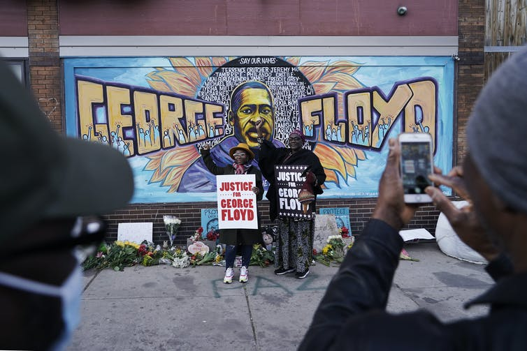Two people stand holding signs that read 'Justice for George Floyd' in front of a mural depicting his face and name
