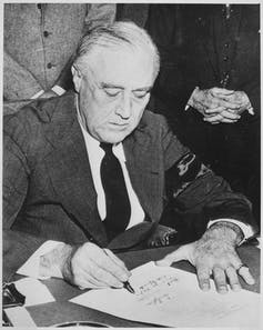 A man in a coat and tie signs a document.