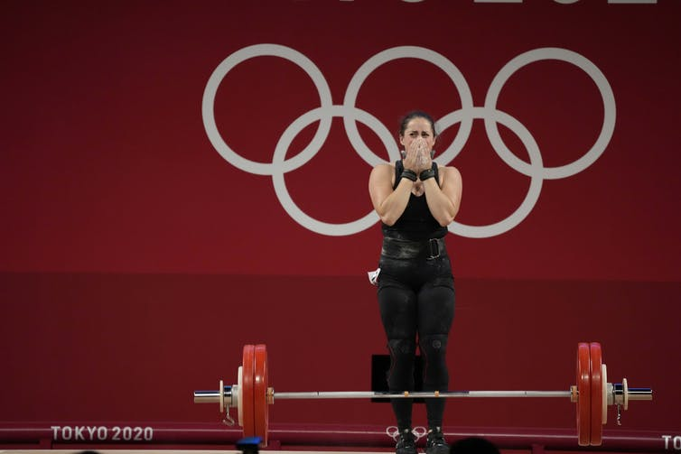 Woman standing behind weightlifting barbell covers the lower half of her face, looking overcome with emotion.