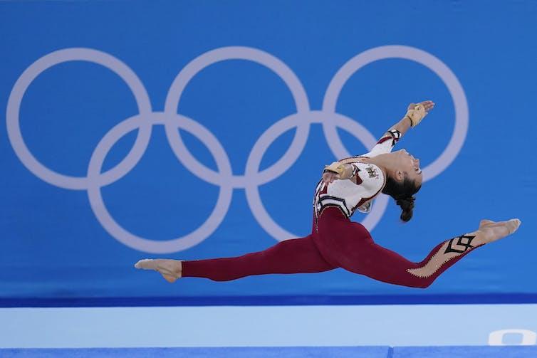 Woman in full unitard doing a split jump in midair.