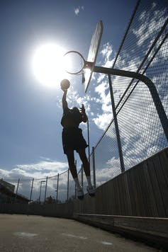 A basketball player jumping to make a shot