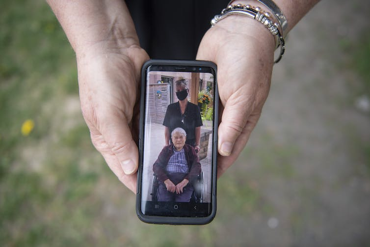 A smartphone in a woman's hands, showing a picture of a woman in a mask and a man in a wheelchair