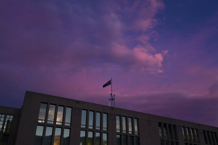 A pink sunset lights up then sky over Parliament House in Canberra.