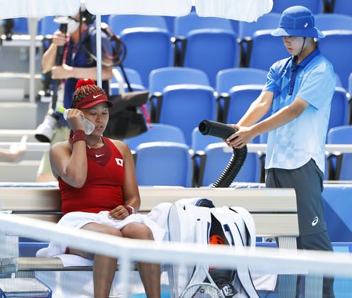 Tennis player Naomi Osaka holds an iced water bottle to her cheek during a cooling break