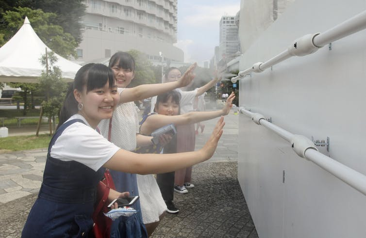 Girls stand at a misting station at the beach volleyball Olympic venue in Shiokaze Park, Tokyo