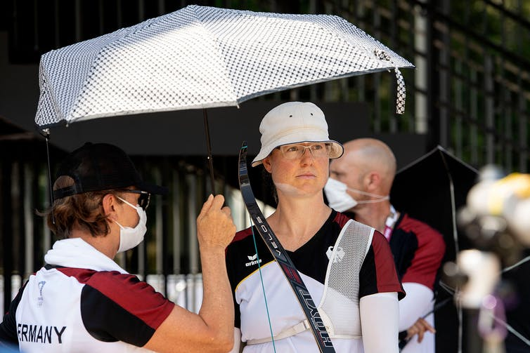 German archer Lisa Unruh is protected from the heat with a parasol