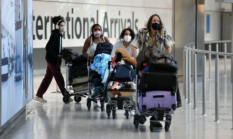 Travellers pushing luggage on trolleys at an airport