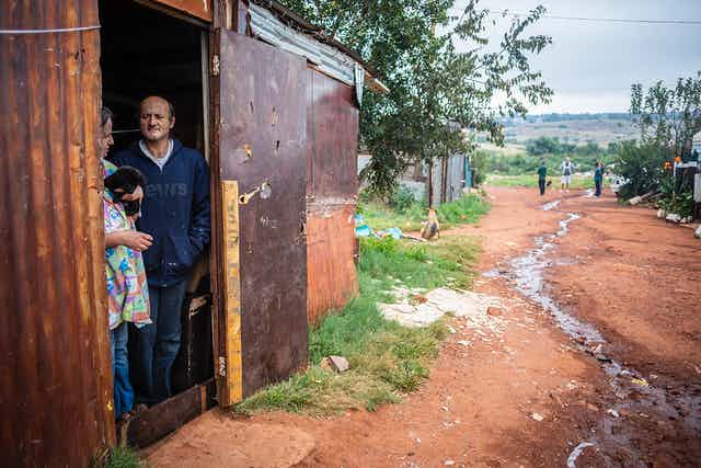 A woman and a man stand in the doorway of a shack, with waste water running down the unpaved road
