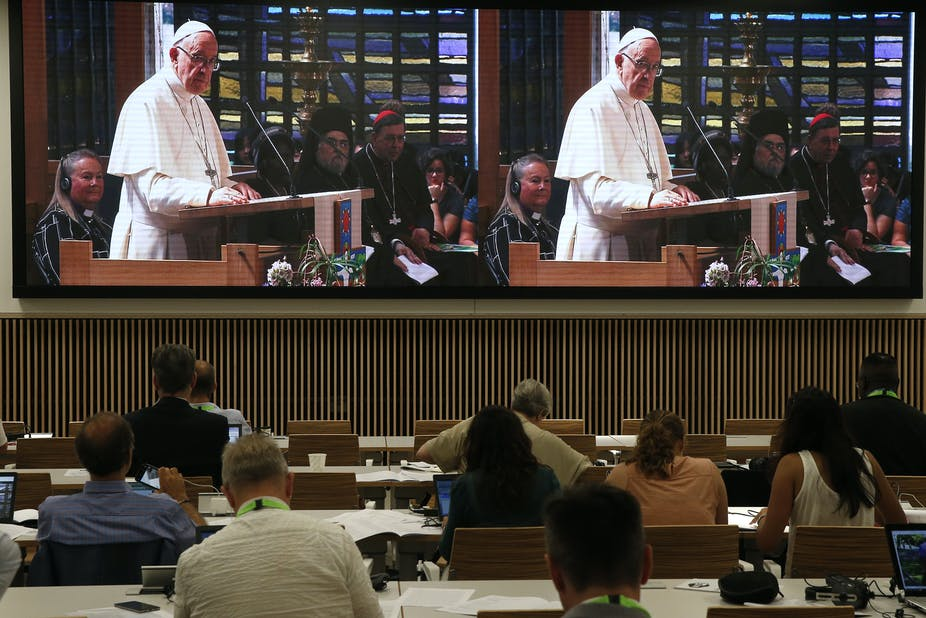 Journalists watch on a big screen as Pope Francis addresses the World Council of Churches.