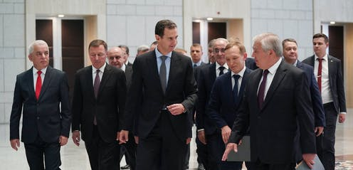 A group of men in suits surround Syrian president, Bashar al-Assad, and Russian special envoy Alexander Lavrentiev at a meeting in Damascus, July 2021.