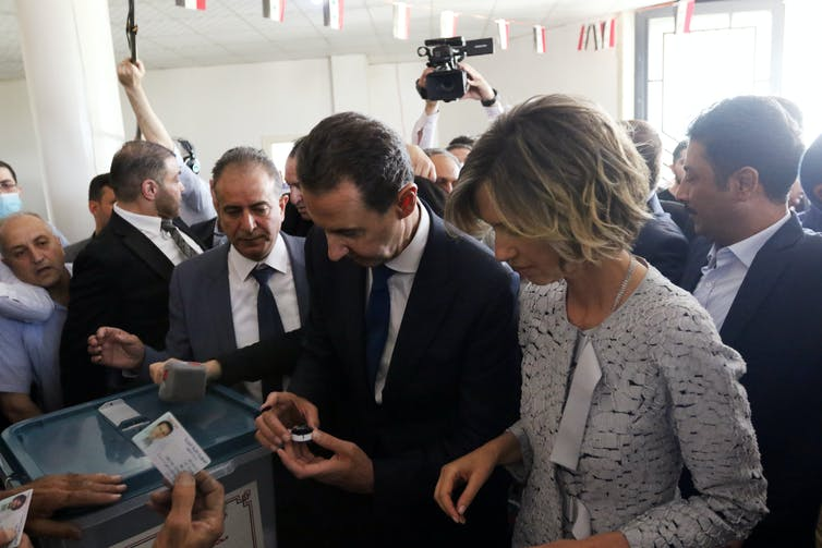 Syrian president Bashar al-Assad and his wife Asma cast their votes during the 2021 presidential election at a polling booth in Damascus, Syria.