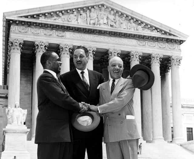 Thurgood Marshall, center, and two other men stand in a 1954 photo on the steps of the U.S. Supreme Court