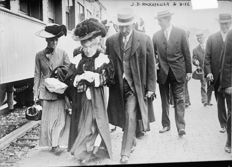 Wealthy people walk alongside a train in the early 1900s