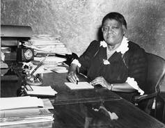 A woman sits at a desk surrounded by papers in an old photograph