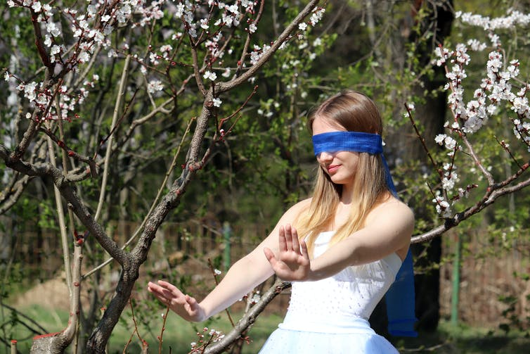 A blindfolded woman stands in a park with her hands held out in front of her