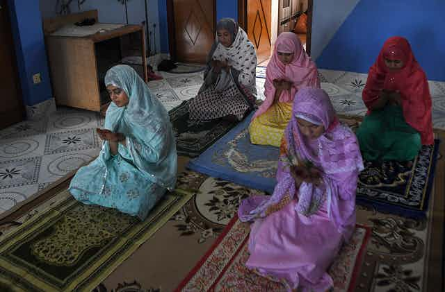Family members offer a special prayer in their home during Eid-al-Fitr, which marks the end of Islamic holy fasting month of Ramadan.