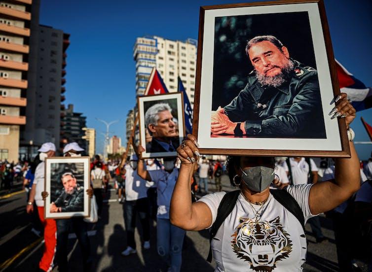 Manifestantes en la calle sostienen fotografías de líderes cubanos