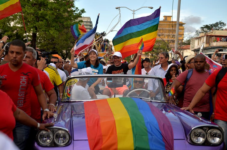 Mariela Castro rides in a car decked out in pride flags surrounded by crowds in a pride parade