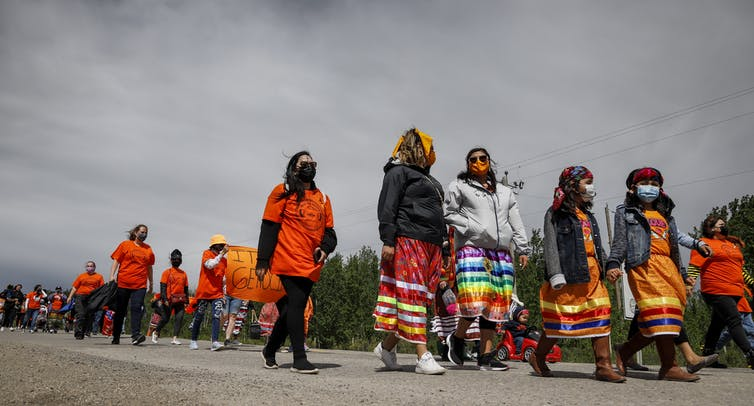 A group of people in orange shirts and ribbon skirts is seen walking down a road.