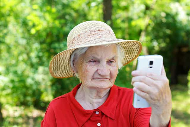 Elderly lady wearing hat looking confused at smartphone