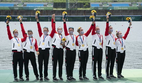 Eight rowers hold up flowers and wave to the crowd after receiving their gold medals.