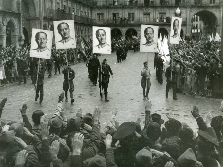 Francoist demonstration in Salamanca (1937) with the paraders carrying the portrait of Franco in banners and the populace pulling the Roman salute.