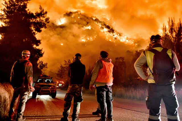 Firefighters look up at a hillside engulfed in fire.