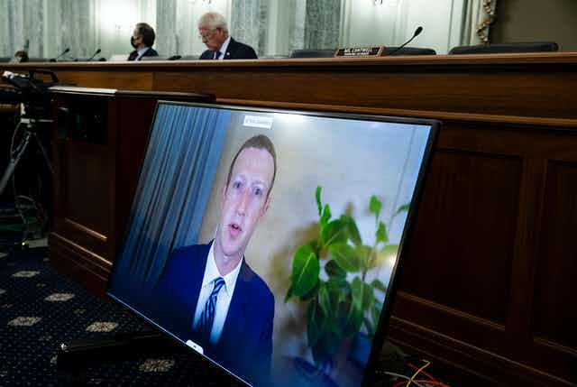 a large video screen with a man's face on it is propped against a large wooden bench behind which sit two men