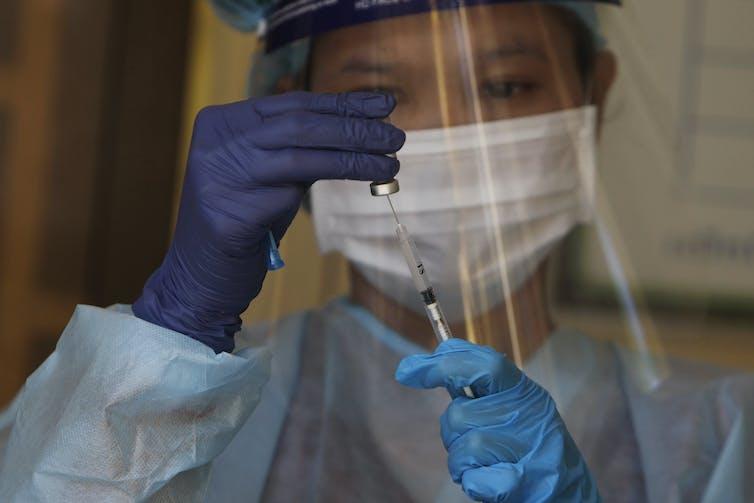 Trabajador sanitario preparando una dosis de vacuna contra la covid-19