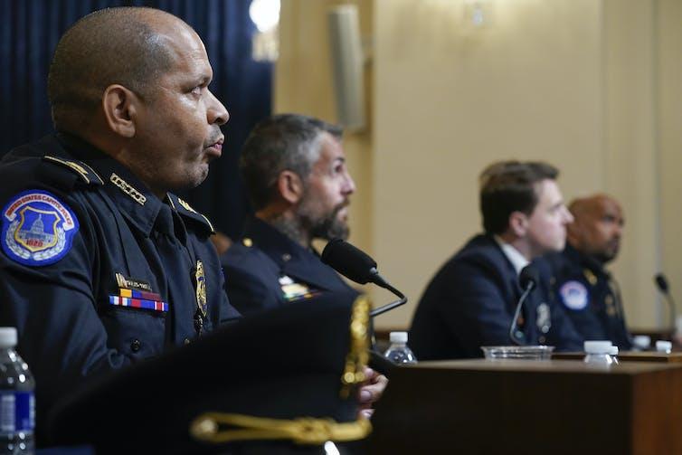 Cuatro policías sentados en una mesa en una audiencia del Congreso.