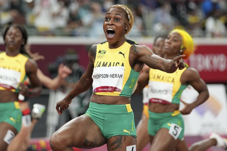 Thompson-Herah reacts with joy with her arms outstretched while her teammates cross the finish line in the background.