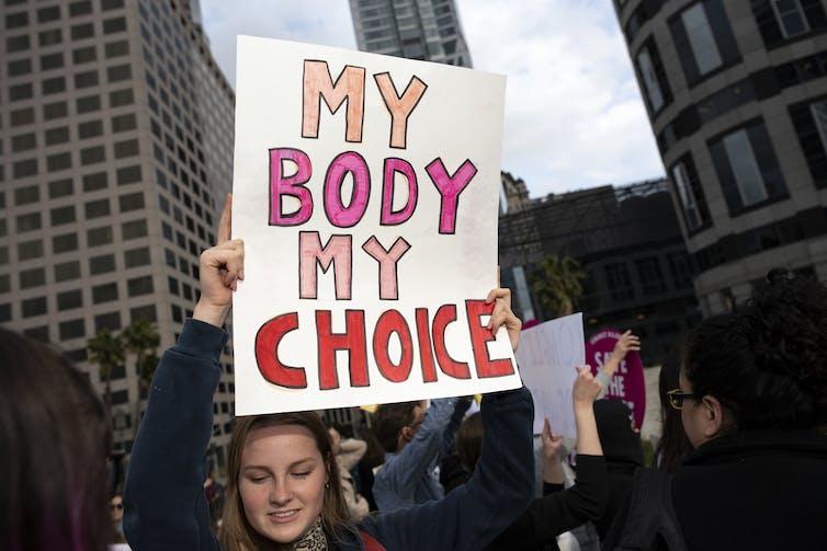 An activist seen holding a placard that says, 'My body My Choice.'