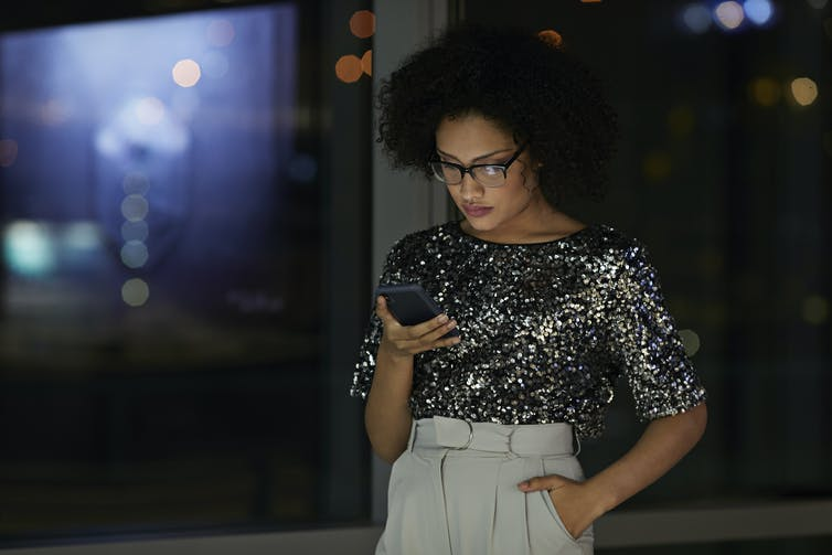 woman checks her phone against backdrop of windows at night