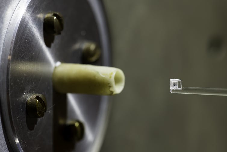 A small green fleck inside of a clear cube sitting on a stand in front of the nozzle of a scientific instrument.