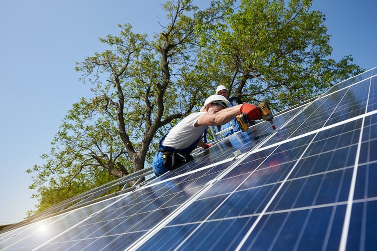 Person installing rooftop solar