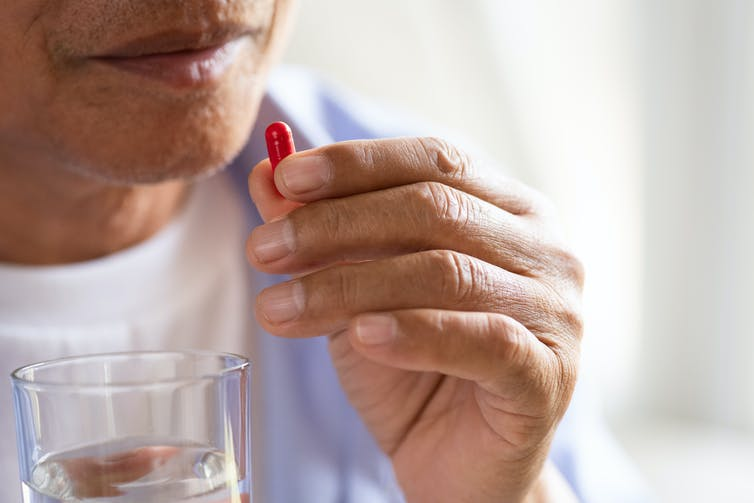 Older man holds pill to his mouth in one hand and a glass of water in the other.