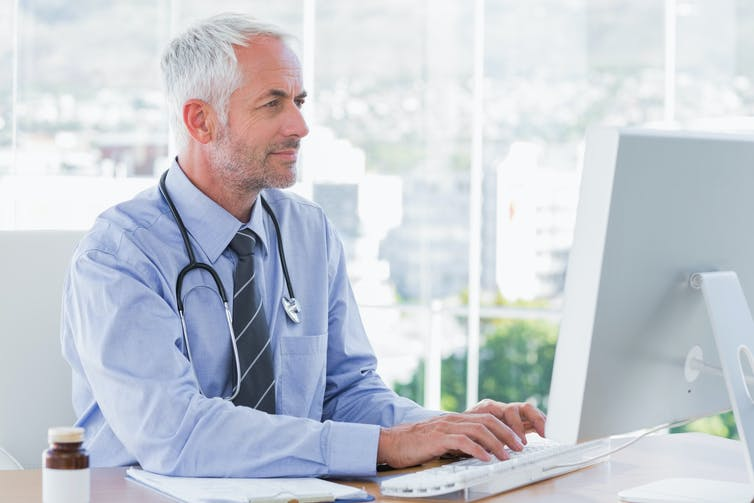 Male doctor types at his computer.