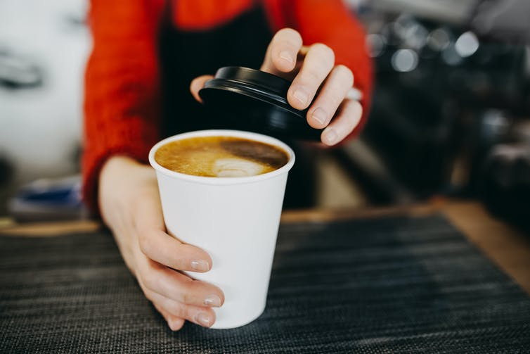 A barista puts a lid on a cup of takeaway coffee.
