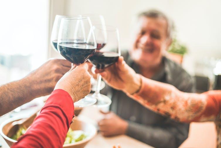 people clink wine glasses