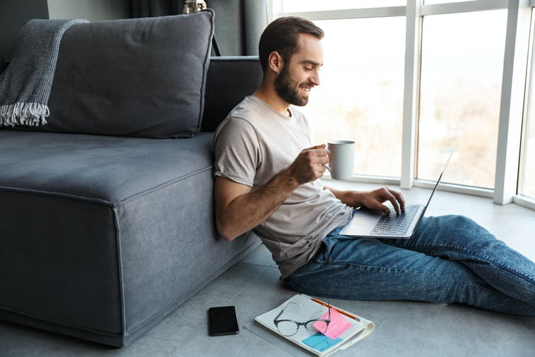 A man sits on the floor on his laptop, with a cup of coffee in hand.