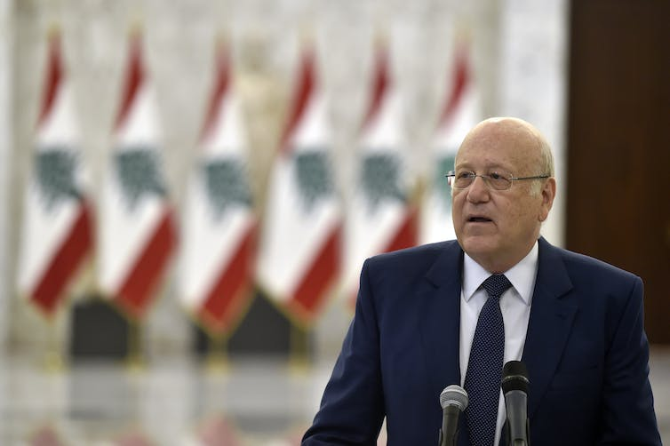 An old man in a suit speaks into microphones in front of a row of Lebanese flags.