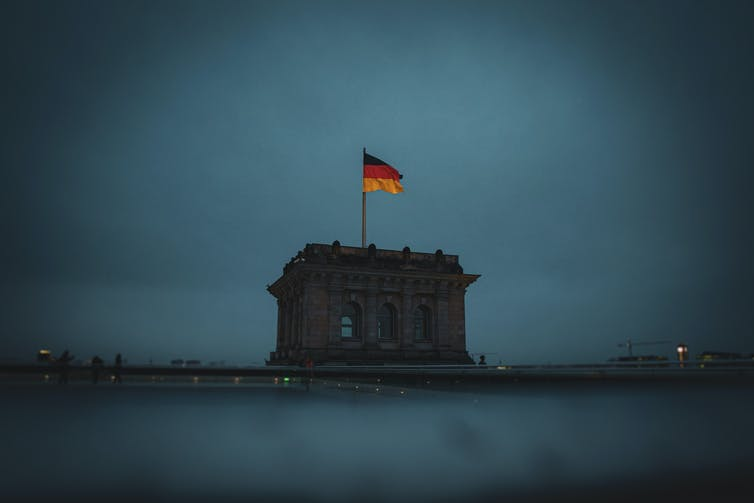 German flag on top of the Reinchstag at dusk