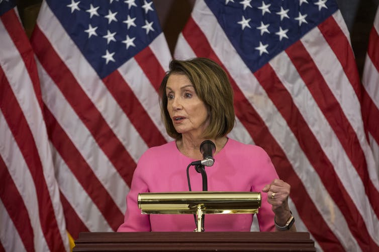 Democratic House Speaker Nancy Pelosi at a lectern in front of American flags.