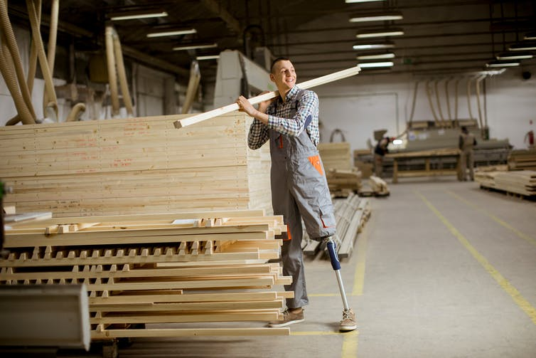 A man with an artificial leg moves lumber in a warehouse.
